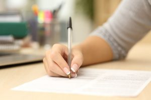 50532400 - close up of a woman hand writing or signing in a document on a desk at home or office
